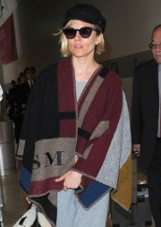 Sienna Miller kept warm in style with a personalized Burberry blanket poncho for a flight out of LAX.