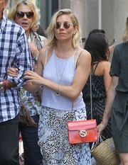 Sienna Miller topped off her strolling outfit with a pair of round shades.