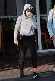 Sofia Richie teamed her hoodie with black sports pants by Balmain.