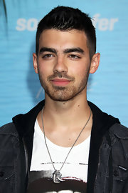 Joe Jonas rocked a silver tooth pendant necklace to the premiere of ;Soul Surfer.'