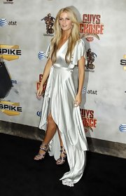 The blonde beauty wore a satin wrapped dress with a rise and fall hemline that showed off her metallic platform sandals.
