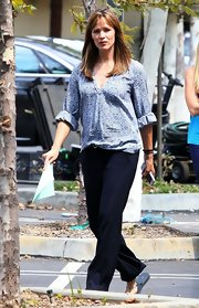 Jennifer chose a printed blouse to pair with her dark navy trousers while on set.