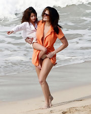 Stephanie Seymour covered up with an orange terry cloth robe while enjoying a day at the beach.