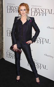 She's carrying a purple leather 'envelope' clutch that matches her shoes and accent handkerchief perfectly.