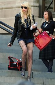 Taylor carried a bright red studded tote on the set of Gossip Girl.