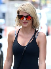 Taylor Swift put on a pair of orange Carrera shades as she departed her gym.