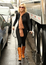 Tori Spelling braved the rain in a pair of tan knee high boots.