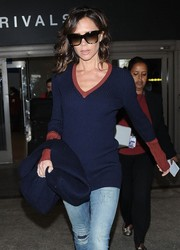 Victoria Beckham shielded her eyes with a pair of butterfly sunnies from her own label while arriving on a flight at LAX.