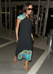 Posh Spice brought some whimsical glamour to LAX with this paisley-embellished one-shoulder frock from her Victoria, Victoria Beckham label.