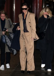 Victoria Beckham went androgynous in a bold-shouldered beige suit from her own label while out in New York City.
