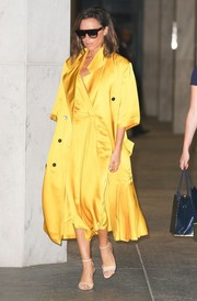 Underneath her coat, Victoria Beckham wore a classic satin wrap dress in the same yellow hue.