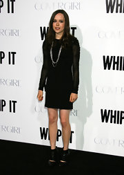 "Ellen looked sophisticated and modern in a sheer-sleeve black ""Slim Grommet Dress"" with a layered silver chain necklace and funky cutout booties."