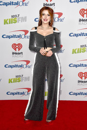 Matching wide-leg trousers with white ruffle detailing completed Bella Thorne's outfit.