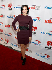 Demi Lovato opted for a simple burgundy sweater dress, which she styled with an oversized black belt, when she attended KISS FM's Jingle Ball.