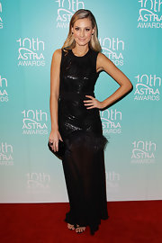 Laura Dundovic exuded understated glamour at the Astra Awards in a sleeveless black evening dress with a sheer skirt and feather detailing.