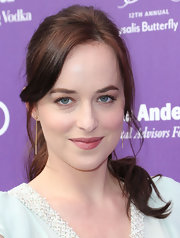 Dakota Johnson accessorized with simple yet elegant gold dangle earrings.