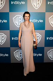 Emily Watson accessorized her nude gown with a gold chain necklace and a bronze clutch.