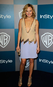 Malin Akerman accented her stunning drop-waist dress with a gilded tube clutch and matching heels.