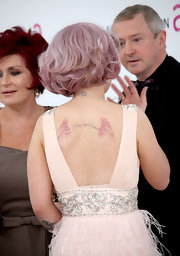 Kelly has pink feathers tattooed on her back with script in the center.