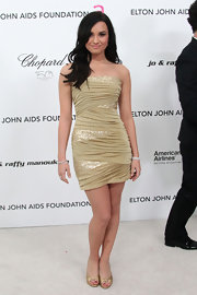 Demi completed her wrapped strapless mini dress with a pair of simple metallic gold peep-toe pumps.