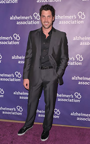 Maksim walked down the purple carpet at a fundraiser in Beverly Hills wearing a slate gray suit. He added a casual touch with black sneakers.