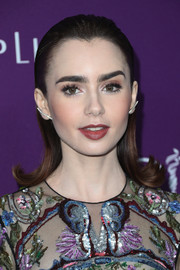 Lily Collins attended the Costume Designers Guild Awards wearing a slicked-down hairstyle with flippy ends.