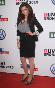 Edita posed on the red carpet in gray satin pumps.