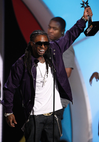 Lil Wayne accepted his BET Award in a purple zip-up jacket and white tee.