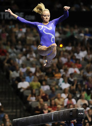 Nastia's pony tail flies behind her, as she competes on the beam,