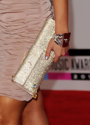 Cheryl Burke added sparkle to her red carpet look with a dazzling gold clutch. The crystal-embellished clutch featured a gold chain.