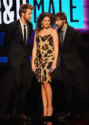 Hillary Scott slips into leopard print during the AMAs. This corset dress is wild with her pink lips and curled locks.