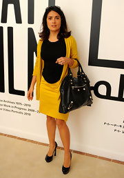 Salma Hayek wears a yellow cardigan to match her yellow and black attire.