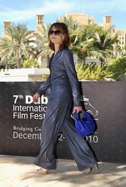 Isabelle added a pop of color to her gray suit with a violet leather tote.