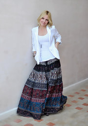 Emma poses sweetly in a white blazer and long ethnic print skirt.