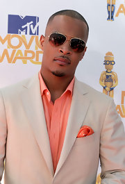 T.I. showed off his classy style in a tan sport coat and coral shirt, which he paired with aviator shades.