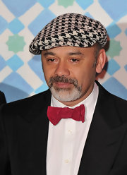 A houndstooth newsboy cap and red bow tie give Louboutin's tux a whimsical twist.