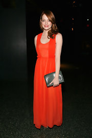 Emma Stone punctuated her lovely tangerine gown with a forest green clutch.