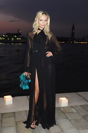 Natasha Poly was sexy chic in a sheer black gown with a cinched waist and a thigh high split.
