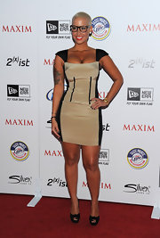 Amber Rose shows off her figure at the Maxim Hot 100 Party in a black and nude cocktail dress and geek-chic glasses.