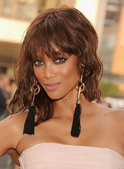 To duplicate Tyra Banks' bewitching eye makeup look, start at the inner corners of eyes and sweep a black liquid liner brush gently along the upper lash line, flicking the brush up slightly past the outer corners. Use a black eye pencil to line along the lower lash lines and along the inner rims of eyes. To finish the look add a few coats of mascara.