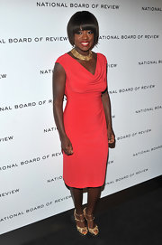 Viola Davis was a sight to behold in a vibrant coral knit dress with gold accessories.