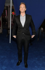 Neil wears a slim fitting black suit with an elegant sheen. He opted to go without a tie for this stylish ensemble.