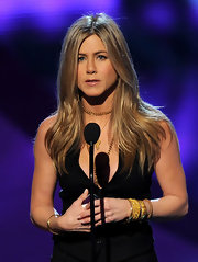 Actress Jennifer Aniston shined on stage at the People's Choice Awards in vintage gold cuffs and bangle bracelets.