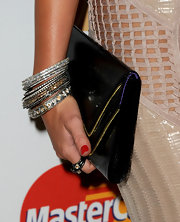 Miley Cyrus attended the 2011 Pre-Grammy Gala carrying a zip-embellished patent clutch.