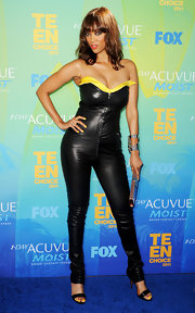 At the 2011 Teen Choice Awards, Tyra Banks appeared to be making a play for the role of Catwoman in a skintight black leather jumpsuit with sweetheart bodice trimmed in yellow silk. She teamed the look with, what else, kohl-rimmed cateye and sultry red lips.