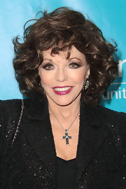 Joan Collins looked marvelous in a cross pendant necklace at the UNICEF Ball.