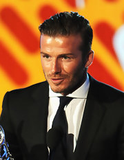 A slicked back David Beckham wore a solid navy blue tie with his black tux.