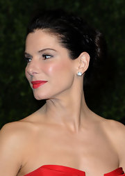 Sandra Bullock paired her twisted bun and radiant red lips with classic diamond stud earrings.