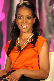Shaun Robinson gave her orange blouse a ladylike finish with a double strand pearl necklace.