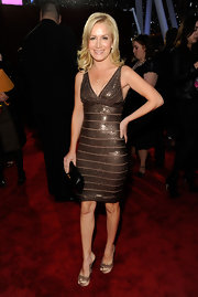 Angela Kinsey distracted from her ultra-sexy gold bandage dress with a black clutch.